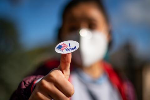 "Young woman with mask holding a ""I Voted"" sticker. The presidential election shows the standoff in our national politics is growing more serious, says Tufts political scientist"